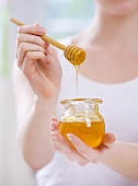 Junge Frau hält Honigglas und Honiglöffel