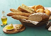 Assorted bread and bread rolls in bread basket, olive oil beside it