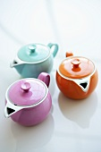 Three coloured teapots