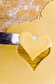 Cut-out heart-shaped biscuit on knife