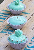 Three turquoise cupcakes with silver dragees
