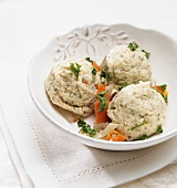 Matzah Balls with Carrots and Parsley in a White Bowl