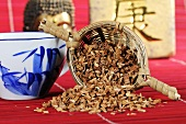 Millettia stem in tea strainer with bowl of tea