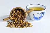 Saposhnikovia root in tea strainer, bowl of tea
