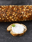 Multigrain baguette and baguette slice with cream cheese and basil leaf