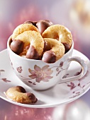Chocolate-dipped vanilla cresecents in a cup and saucer