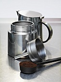 Espresso maker and scoop full of ground coffee