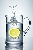 Lemon falling into jug of water