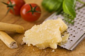 Parmesan with grater, grissini, tomatoes and basil