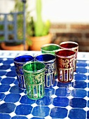 Several coloured glasses on mosaic table