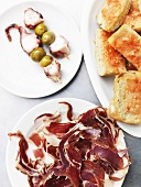 Octopus and olives on cocktail sticks, bread and raw ham (Spain)