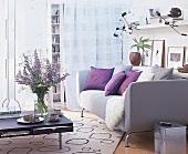 Wohnraum: helles Sofa, darüber Regal als Ablagefläche