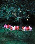 Verschiedenfarbige leuchtende Papierlaternen auf Tischen und in Bäumen, im Garten mit Abenddämmerung