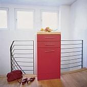 Roter Möbelurm endet zwischen der Treppenreling aus Metall