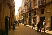 People walking in an alley in old town of Alghero, Sardinia, Italy
