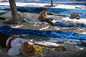 Fisherman mending nets on port of Palma, Mallorca, Spain