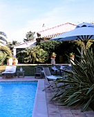 Sun loungers and wicker furniture at swimming pool of villa in Saint-Tropez, France