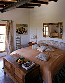 Rustic bedroom with beamed ceiling, wooden chest and tiles