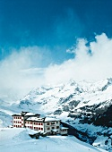View of hotel in snow capped mountains, Valais, Switzerland