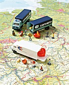 Toy cars and human figurines on land map depicting long distance relationship