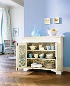 geöffnete Anrichte mit Toile de Jouy Muster im Wohnzimmer, Wand blau