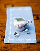 A small cream jug on a light blue napkin with a silver spoon