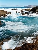 Schaeumende Meeres - Brandung an einer Fels - Kueste