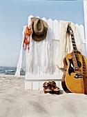 Kleidung hängt am Holzzaun am Strand, Schuhe, Gitarre