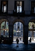 Walkers in Gothic Quarter of Barcelona with arcades