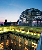 The dome of Reichstag illuminated at dusk in Berlin, Germany