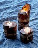 Drei Kerzen brennen in ausgehöhlten Holzscheiten