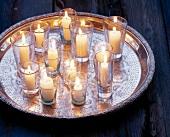 Kerzen in  Wassergläsern stehen auf einem Silbertablett verteilt