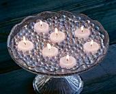 Teelichter zwischen Glasmurmeln auf einer Glas-Etagere