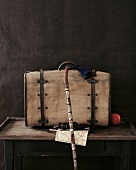 Close-up of old suitcase, walking stick, map, binoculars, time travel on table