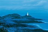 View of Lighthouse, rocky coast at night