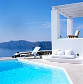View of sun lounger by the pool on white terrace with mountains in background