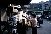 Food stall with steaming pots on street in Shanghai