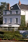 Französisches Landhaus mit Wintergarten im Sonnenschein
