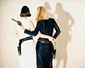Rückansicht von zwei Frauen mit Revolvern und Revolvergürteln