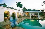 Vies of illuminated villa with pool and palm trees at dawn, Jamaica, Blurred motion