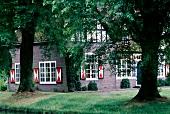Schloss mit einem Wassergraben in Heeze, rotweiße Fensterläden