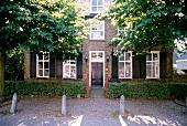 Altes Backsteinhaus in Nuenen, grüne Fensterläden, Hecke, Bäume