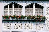 Fenster in Blau mit Hamdwerksarbeit verziert, Blumen, Schweiz