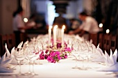 View of large laid white table with flowers, burning candle and glass in Mallorca, Spain