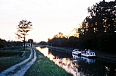 Boats sailing in Canal du Midi at dusk in Aude, France