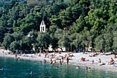 Strand auf Insel Vis in Kroatien mit Bäumen bedeckt, Menschen, fern
