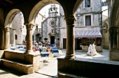 Guests at sidewalk cafe at main square in old town on Korcula island in Croatia