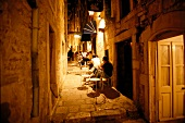 Guests at restaurant in narrow streets of old town on Korcula island, Croatia