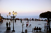 Tourist enjoying sunset at promenade in Taormina, Sicily, Italy
