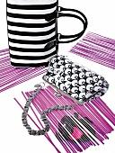 schwarz-weiss-gestreifte Handtaschen auf lila Papierstreifen